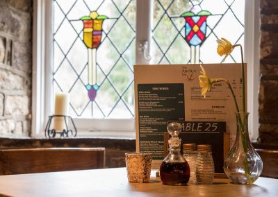 Table and stained glass window at the Anchor Inn, Tintern